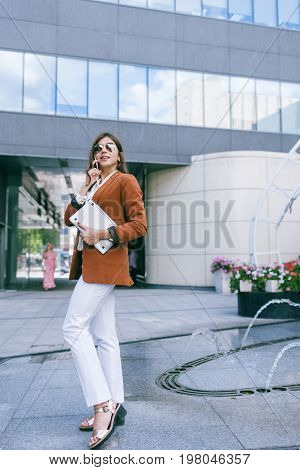 Business negotiations by mobile phone. Stylish workaholic woman on street, busy working lady