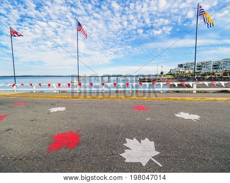 Red and white banners and maple leaves decorate the seaside walk in Sidney Vancouver Island British Columbia to celebrate Canada 150 anniversary