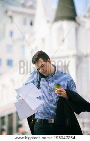Male workaholic at coffee break. Busy man working on street
