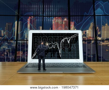 Businessman standing over the computer laptop on the wood table and writing the trading graph at the screen over the blurred photo of trading graph on cityscape background Business trading concept
