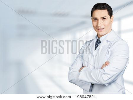 Young male doctor handsome doc looking at camera arms crossed