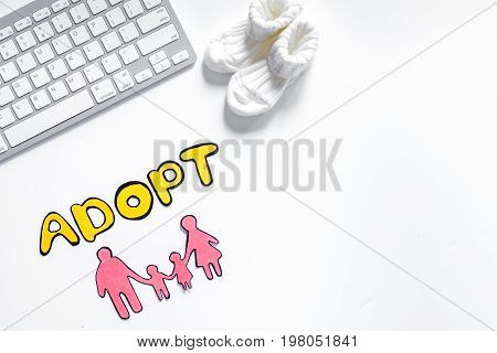 Adopt word, paper silhouette of family on white background top view.