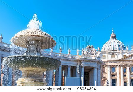 ItalyRome a fountain of St.Peter square with the Bernini's colonnate adn the Basilica facade in the background