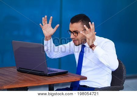 Stressed Angry Young Business Man With Laptop Sitting At Table-