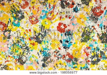 Bright and colorful hand prints on a rough texture wall.