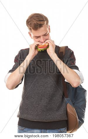 Portrait of handsome teenage student eating sandwich