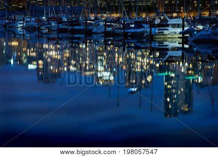 Coal Harbor Night Glitter, Vancouver. Reflections of Vancouver in a calm Coal Harbor next to Stanley Park at twilight. British Columbia.
