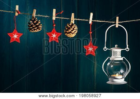 Christmas background. Candle lantern cones and red stars on clothespin on deep blue wooden background with copy space. Christmas or New Year card template.