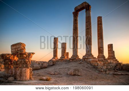 ancient ruins with sun and sunset sky in background (Temple of Hercules in Amman Jordan)