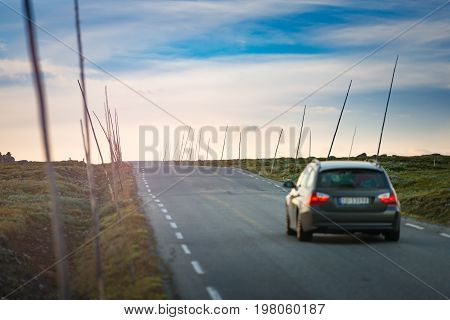 Car on country road in Norway Europe Scandinavia. Auto travel on sunset. Blue sky with clouds.