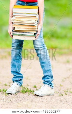young student girl holding big pile of heavy books lower body part. Summer or spring green park in background