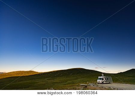 Recreational vehicle on white night in Norway Europe. Hills and dark sky. Travel by RV. Nordic country Europe Scandinavia.