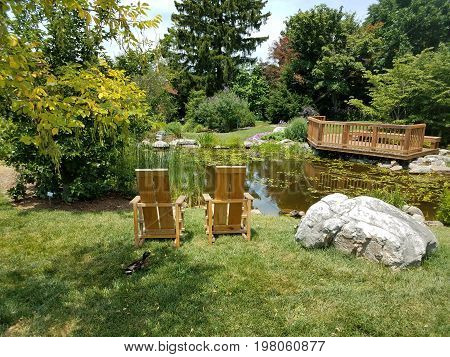 small pond with wood chairs, boulder, wood observation platform and ducks