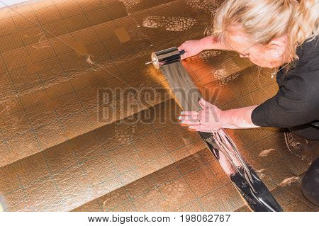 Woman in the laying of plastic laminate or vinyl