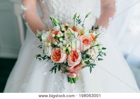 Beautiful Bridal Bouquet With White Roses And Peach Peonies In A Bride Hands In White Dress. Wedding