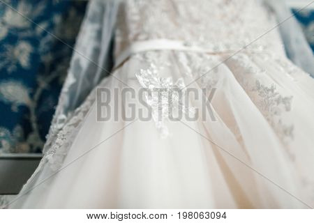 Close-up Image Of Part Of The White Luxury Bridal Dress On The Background Of The Blue Wall. Bottom V