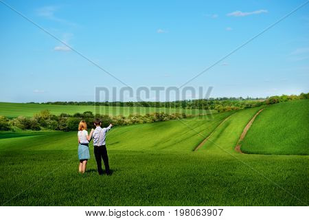 A Young Couple Standing In The Field, The Girl Shows Her Hand To The Sky