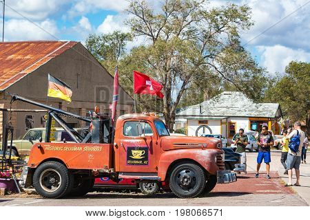 SELIGMAN AZ - SEPTEMBER 16: Tourists take pictures of an old tow truck on Route 66 in Seligman AZ on September 16 2015