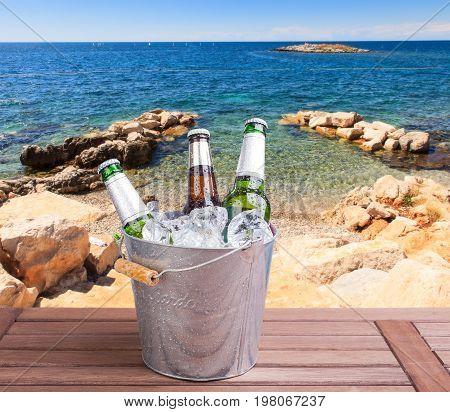 Three unopened bottles of beer inside ice bucket on beach background