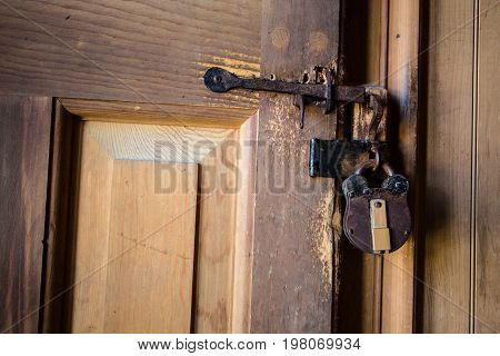 Antique Padlock On Door. An antique 18th century style brass and copper padlock on an old wooden door.