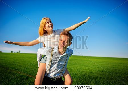 Smiling Man Is Holding On His Back Happy Woman, Who Pulls Out Her Arms And Simulates A Flight Agains
