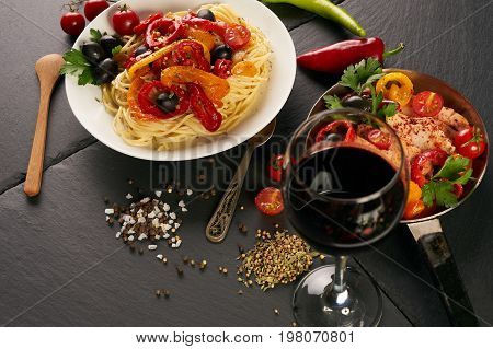 Alfredo pasta - spaghetti with olives chicken cream sauce and fried chicken fillet with vegetables tomato paprica garlic green basil olives and seasoning spices on dark slate table