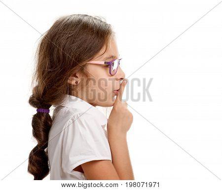 Side view portait of little schoolgirl saying 'shh'