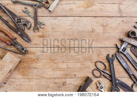 Composition of construction tools on an old battered wooden surface of tools: pliers pipe wrench screwdriver hammer metal shears saws