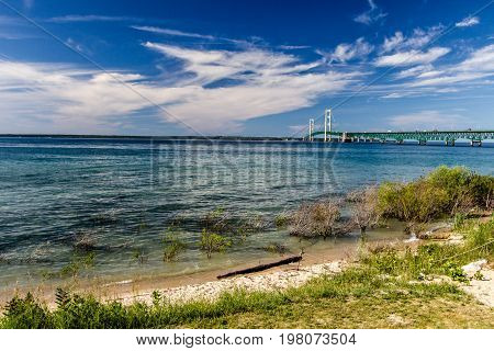 Lake Michigan Beach And Mackinac Beach. The blue waters of Lake Michigan with the landmark Mackinaw Bridge at the horizon. The suspension bridge connects the Upper and Lower Peninsula of Michigan.
