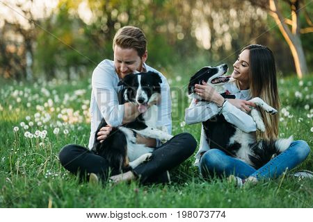 Beautiful couple cuddling and walking dogs outdoors in park