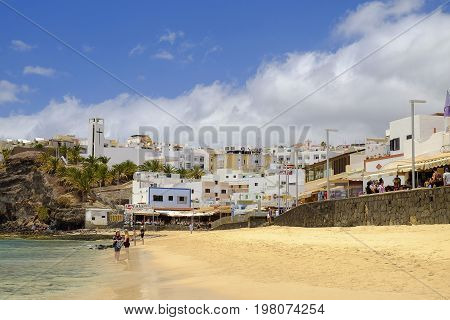 MORRO JABLE FUERTEVENTURA SPAIN - JUNE 14 2017: View on the beach Playa de Matorral and village Morro JAble with unknown tourists on the Canary Island Fuerteventura Spain.
