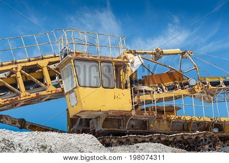 Limestone mining equipment, yellow vehicle. Industrial Gravel Quarry and Sand Stone Refinery