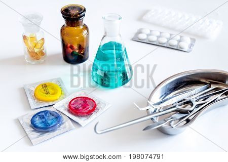 Visit the urologist. Tools and condoms on white background