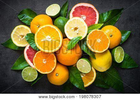 Fresh citrus fruit assortment. Different citrus fruit on black slate table. Fruit food background. Healthy eating and diet.