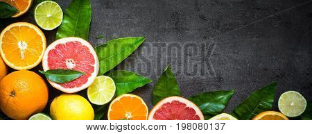 Fresh citrus fruit assortment. Whole and sliced citrus fruit on black slate table. Healthy eating and diet. Long banner format.