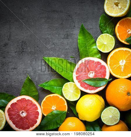 Fresh citrus fruit assortment. Whole and sliced citrus fruit on black slate table. Fruit food background. Healthy eating and diet. Square.