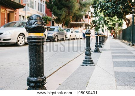 Fencing pillars barriers in a row between the road and the pedestrian zone in the residential quarter of the city.