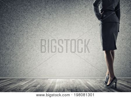 Back view of confident businesswoman in empty concrete room
