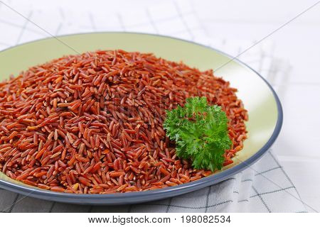 plate of red rice on checkered dishtowel - close up