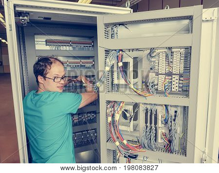 Electrical engineer configuring wires. Electrician repairing substation cubicle. poster