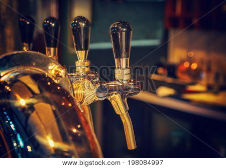 Chromed taps for draft beer in a modern bar. Detail of beer machine beer dispenser close-up selective focus retro style