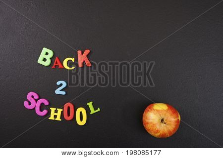 Back 2 school colorful letters and an apple on blackboard background with copyspace for your text. Concept for your design, banner, web, flyer.