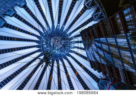 Zenith shot of the cantilever cupola and adjacent buildings, lit at night, in Potsdamer Platz, Berlin.