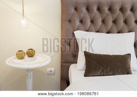 Classic white nightstand with a amp next to a bed with velvet headboard