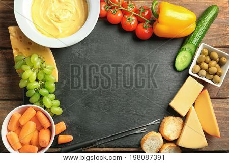Frame made of plate with cheese fondue and different products on slate plate