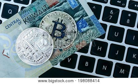 Bitcoin on Kuwait Dinar banknote. Electronic money exchange concept.