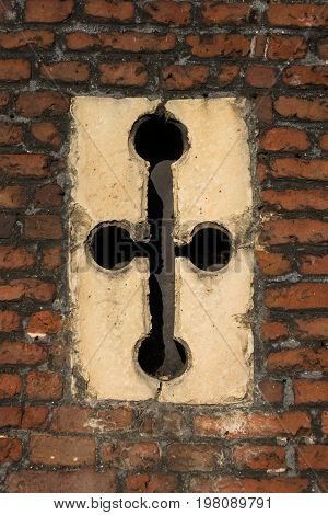 Detail Of Cross-shaped Window Slit In Tudor Architecture Exterior Wall