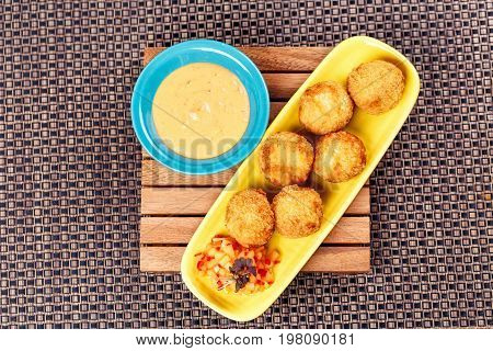 Deep Fried Cheese Balls with sause on yellow plate on wooden board on wicker place mat