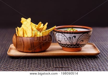 mexico - guacamole and nachos in bowl on wooden plate on wicker place mat