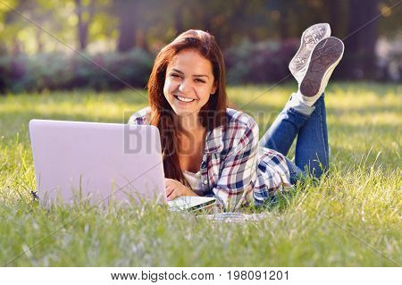 Student Girl Lying Down On The Grass. She Working On Laptop And Smiling